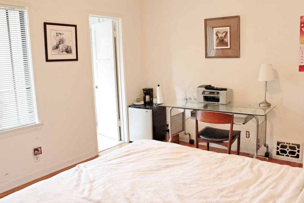 Bedroom has a computer, microwave, small refrigerator and a coffee machine.