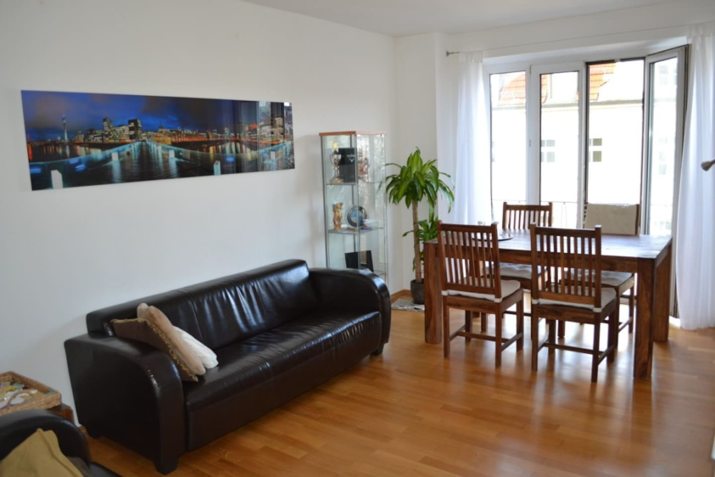 Sunny living room with window front / french balcony facing Herzogstr and its beautiful neighbouring buildings.