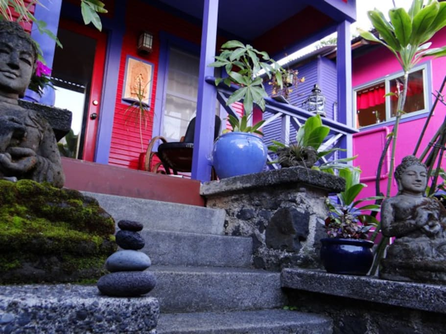 A brightly colored entryway to 'The Sugar Shack' features tropical plants and buddha statuary...