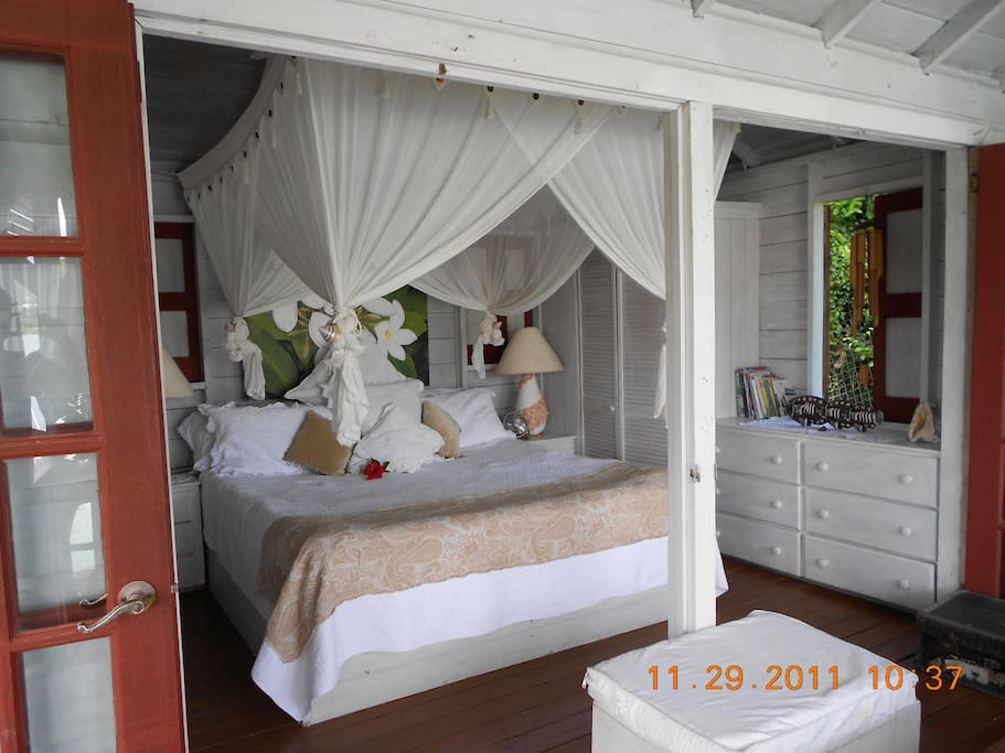 Romantic king size bed in the Bird House bedroom, taken from the lounge settee verandah.  This is the optimum of open air living in a tropical paradise.
