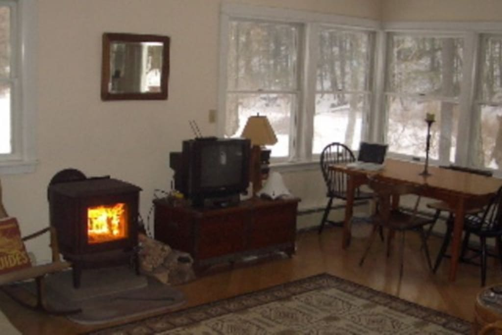 Living room with wood burning stove and dinning table with views of stream and Mountain