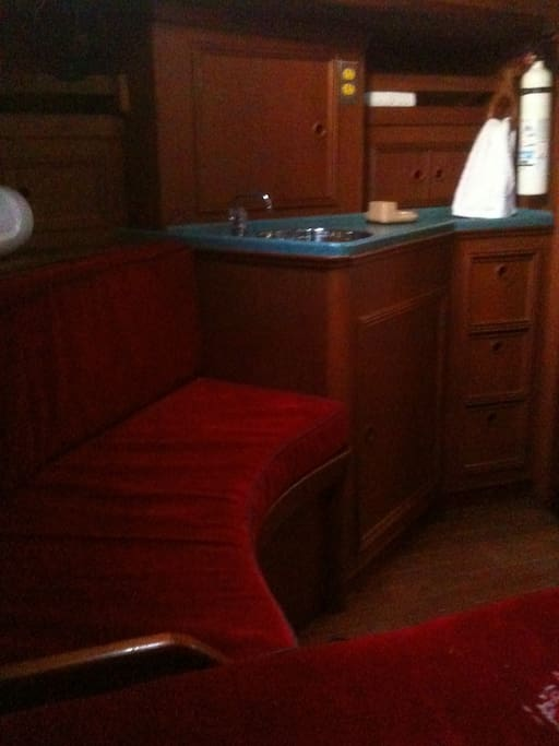 sitting on the captain's bed, located in the stern of the sailboat