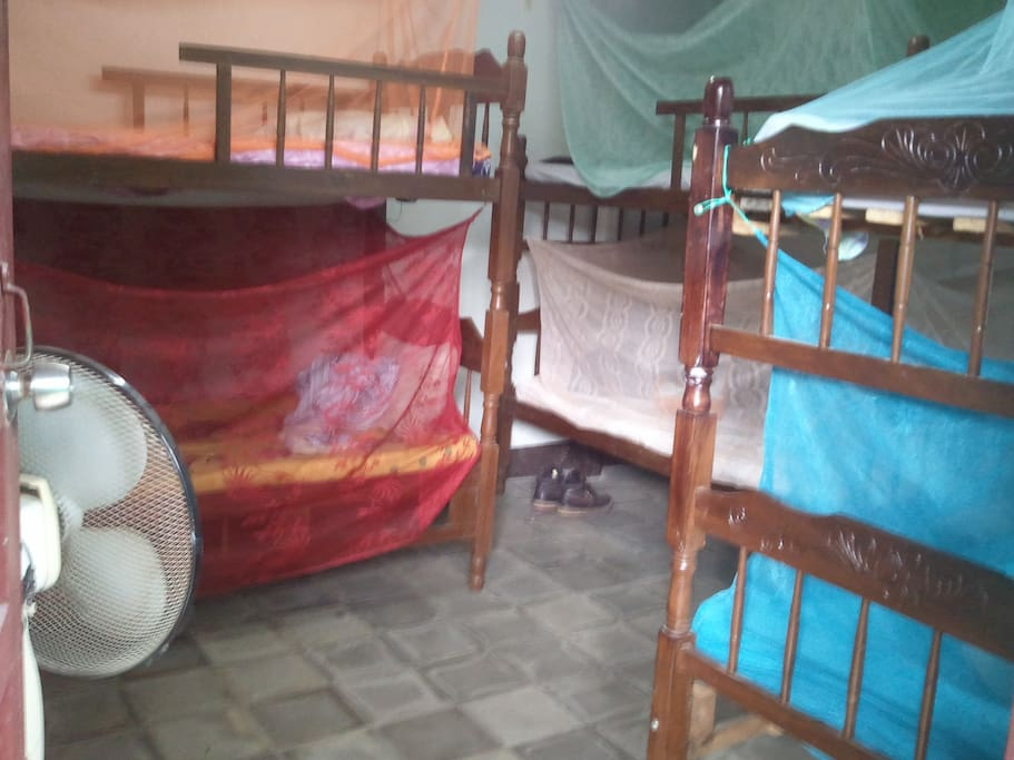 A simple bedroom with mosquito nets and fans.  :-)