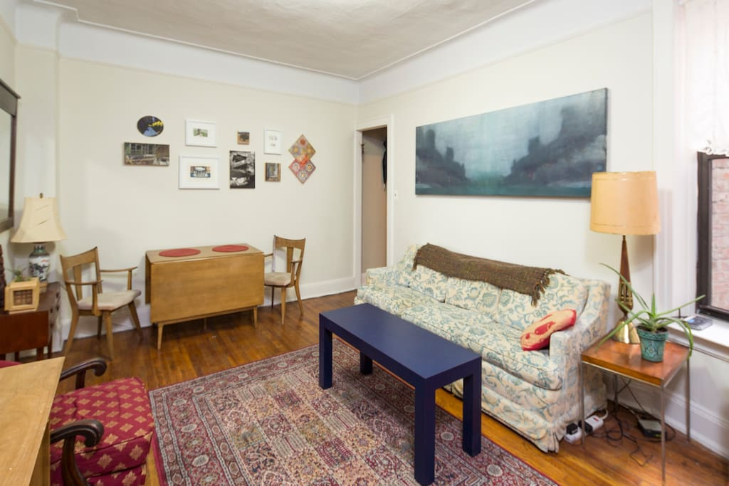 Living Room with drop-leaf dining table and original artwork on the walls