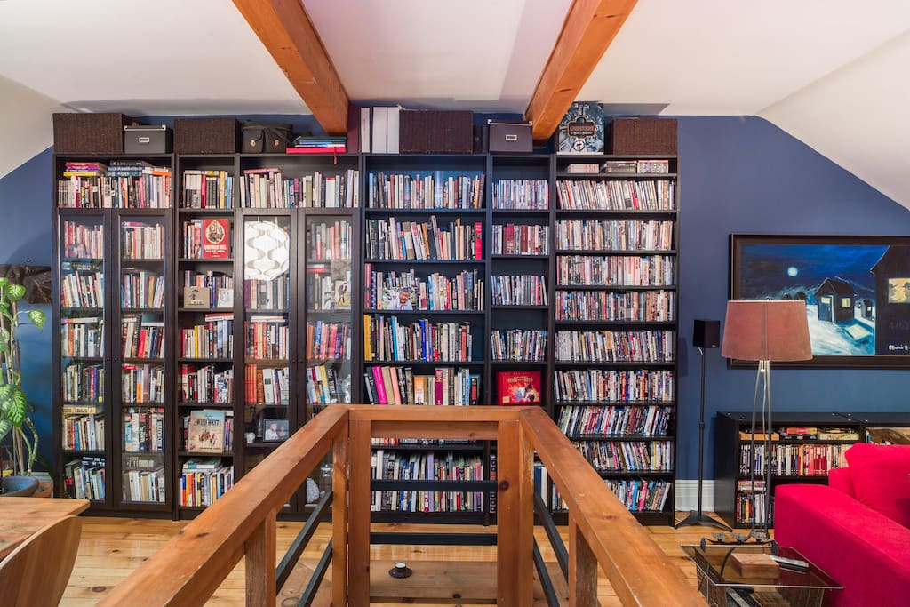 Top of stairway to upstairs loft with wall of books and movies.