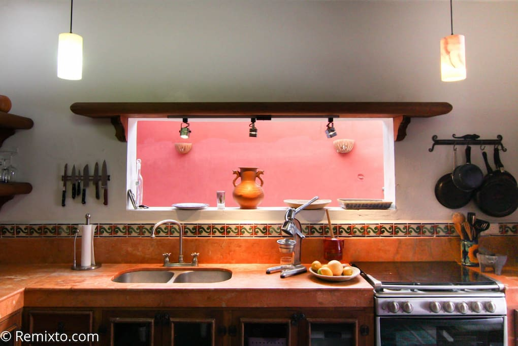 Ticul limestone counter tops adorn a Mexican kitchen with a view to an interior courtyard