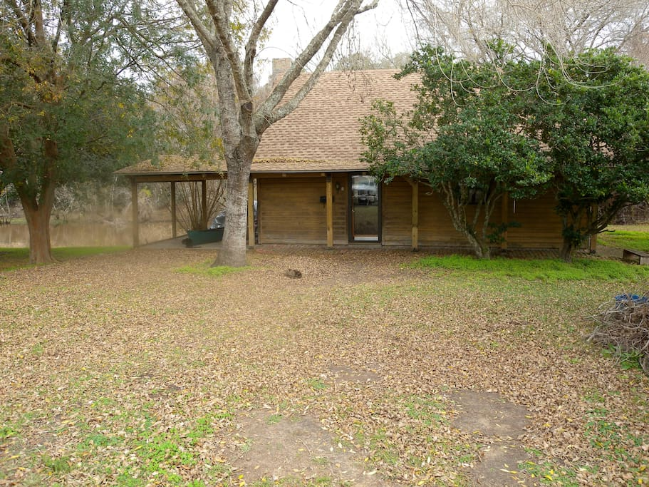 Kayaker's Log Cabin front view with Bayou Teche visible on the left. Ample parking is provided.