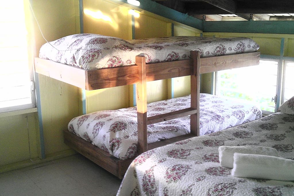 This bedroom consist on a bunk bed (2 twin size) and a.queen size bed.