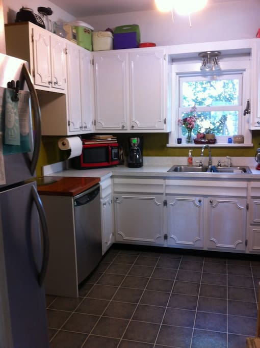 View of kitchen from hallway. Stainless refrigerator and dishwasher. Gas stove. Coffeemaker, microwave, convection toaster oven.