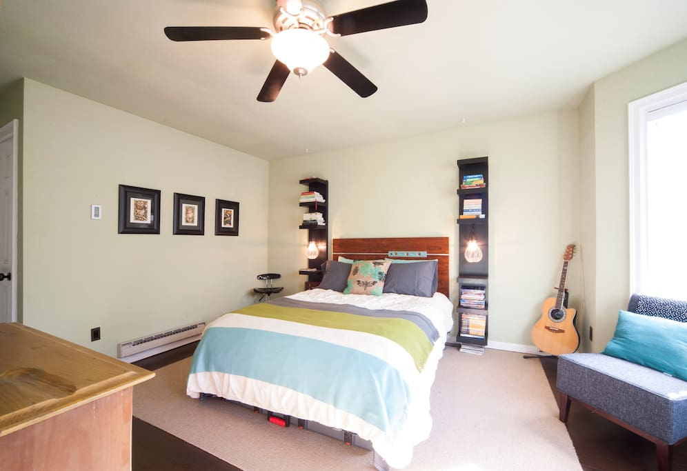 Master bedroom with cork floors, custom headboard, and bookshelves for your stuff.