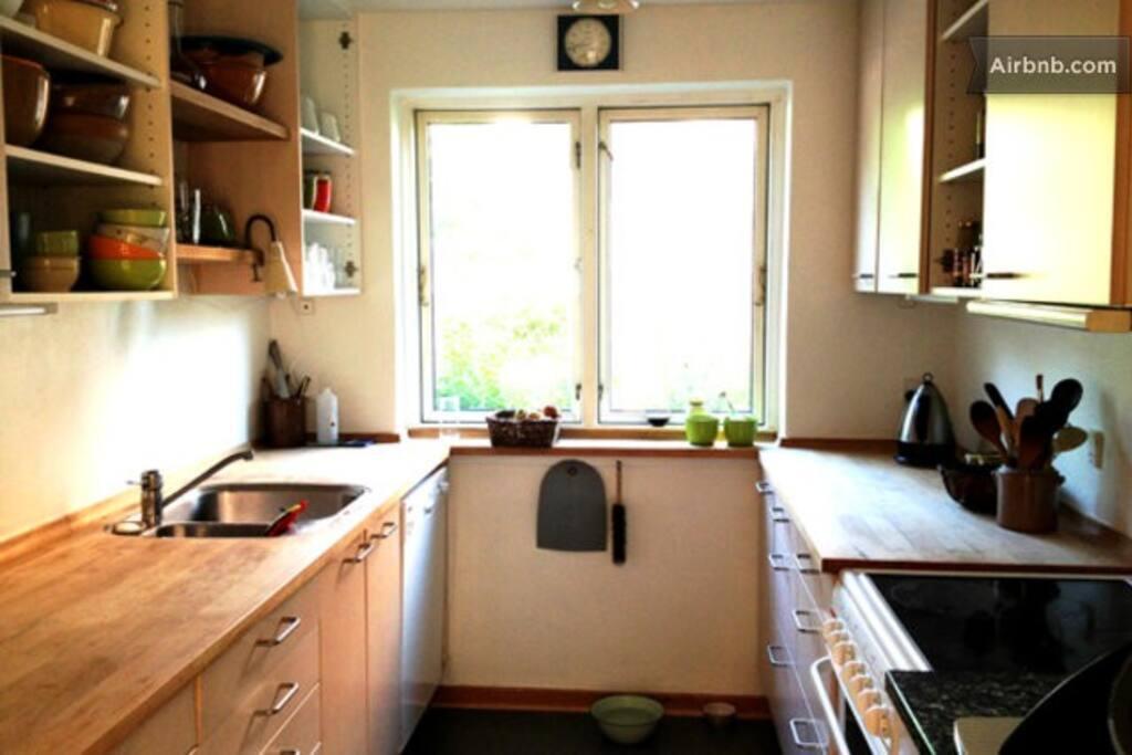 Køkkenet er i stueetagen og der er opvaskemaskine. I må dele køkkenet med os, der bor her.