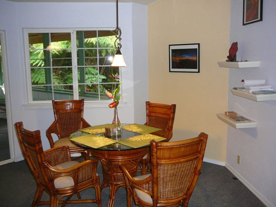 Dining area with view of screened lanai and tropical garden.