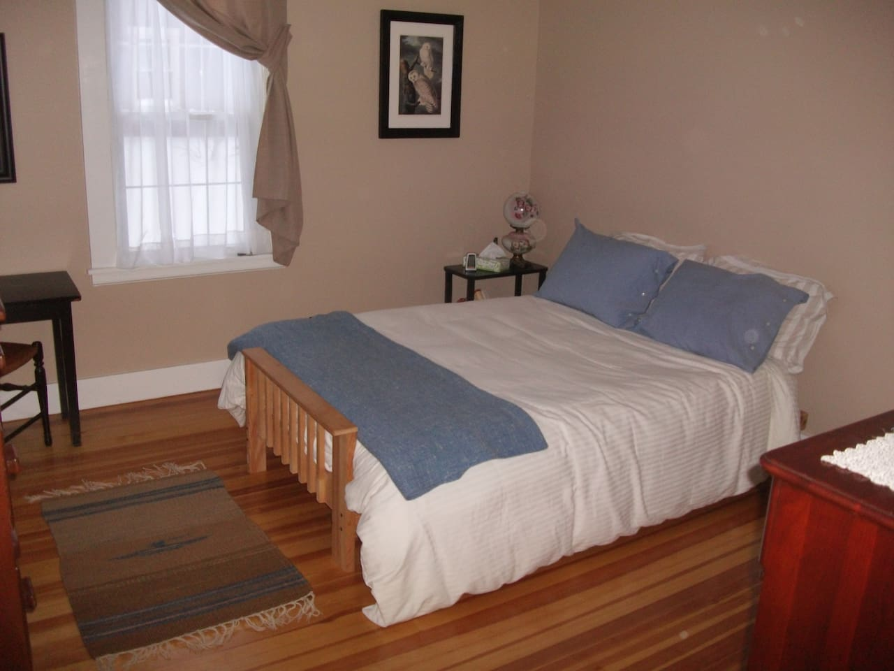 This sunny bedroom has a full size bed, a writing desk, 2 bureaus with mirrors, reading lights, alarm clock,hardwood floors, cedar closet, down comforter and plenty of pillows/blankets.