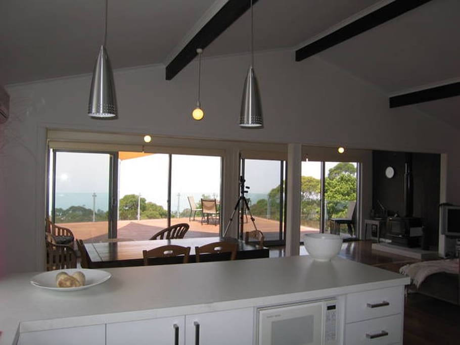 Kitchen looks out on to dining/living/lounge/deck and to the ocean