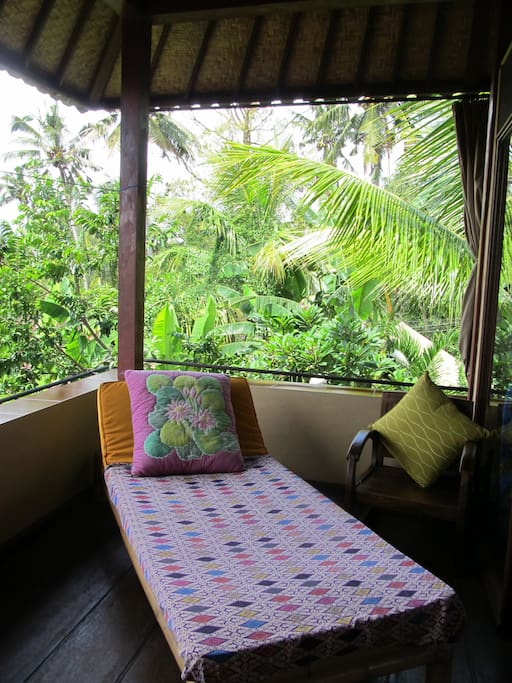 The daybed on the balcony overlooking tropical garden.