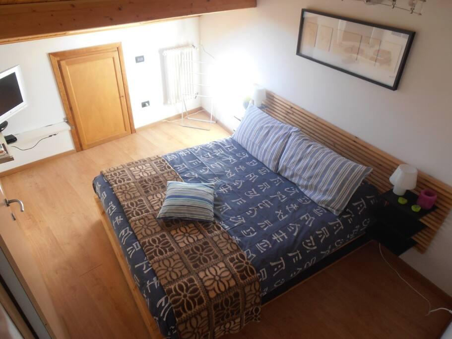 camera da letto matrimoniale accessoriata di lenzuola coperte e copriletto