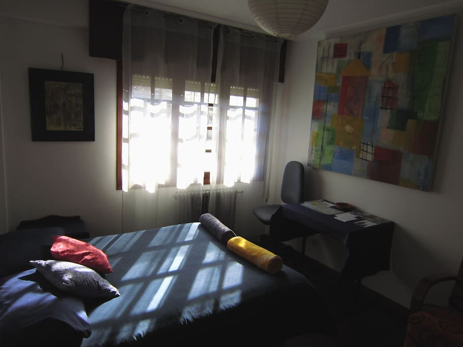 Sunny room in Santiago de Compostela. Wide window, table, swivel chair, decorated, original paintings...