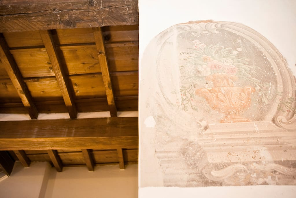 travi in legno rustiche con affresco sul muro.