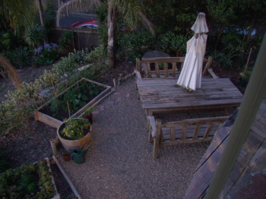 An evening shot looking down from the upstairs deck onto part of the outdoor garden area