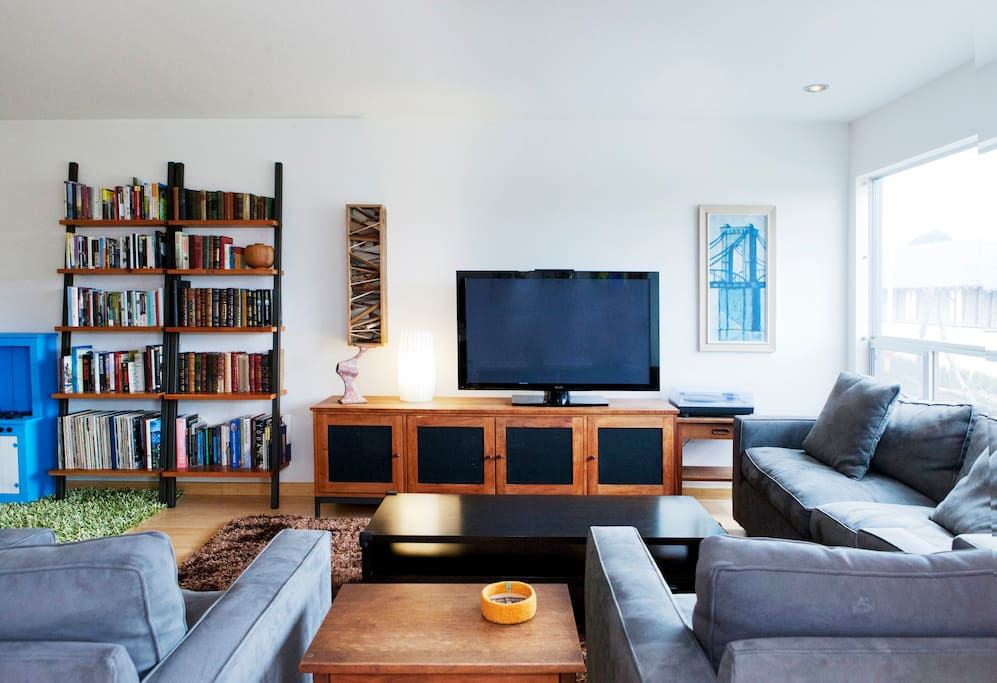 Living room features 50 inch plasma TV, two large chairs, and a couch.
