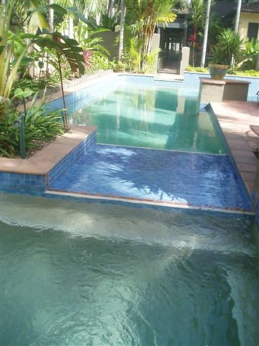 Heated sparkling blue pool and heated spa with lounging chairs and grassy areas