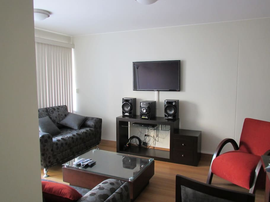 Living room with large wall-mounted LED TV, Stereo,  BluRay DVD, HD Cable TV, 2 sofas, Chair, Coffee table, Lamp