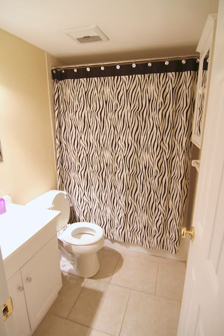 Spacious bathroom with starter shampoo, conditioner, soap, and toilet paper.
