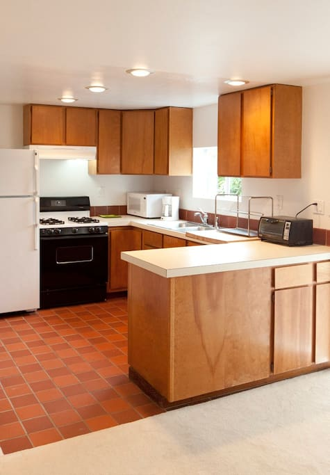 Kitchen with full size refrigerator, gas stove, oven, microwave, toaster oven