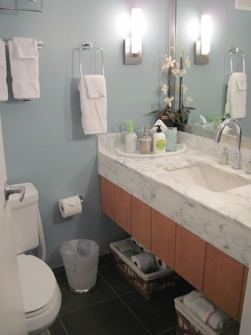 Marble Bathroom w/ tub/shower with baskets of towels & paper supplies for your stay! We also provide dish soap and a scrubbie.
