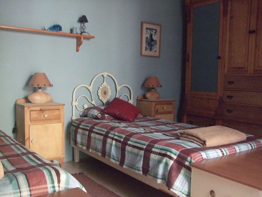 Twin bedroom with sliding door to large terrace. Also has a desk and chair.