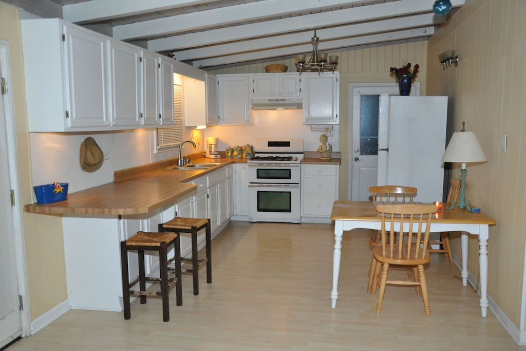 Kitchen with flat surface stove, full size fridge and extra deep sink, dinnerware and cookware.