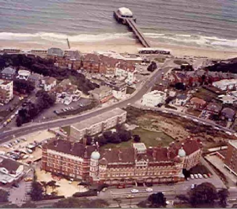 A very old aerial view showing how close the building is to the beach and pier.