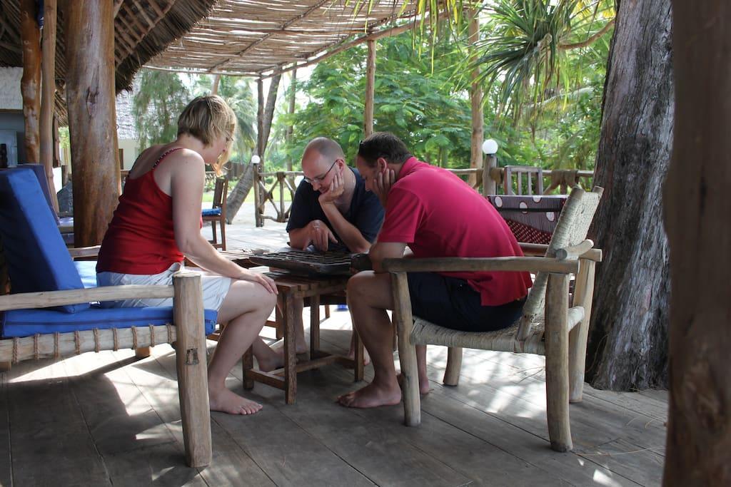 Guests playing Bao at the restaurant veranda