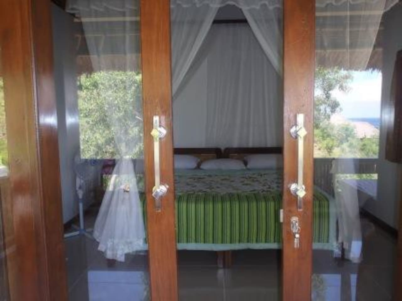 Roomy Bedroom with sliding glass doors and a side window, fully air-conditioned and a stand alone fan
