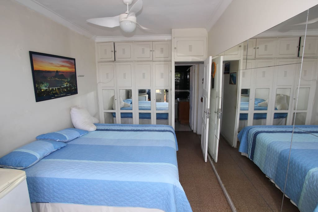 View of room from Veranda. King size bed, mirrors, refrigerator, ba
