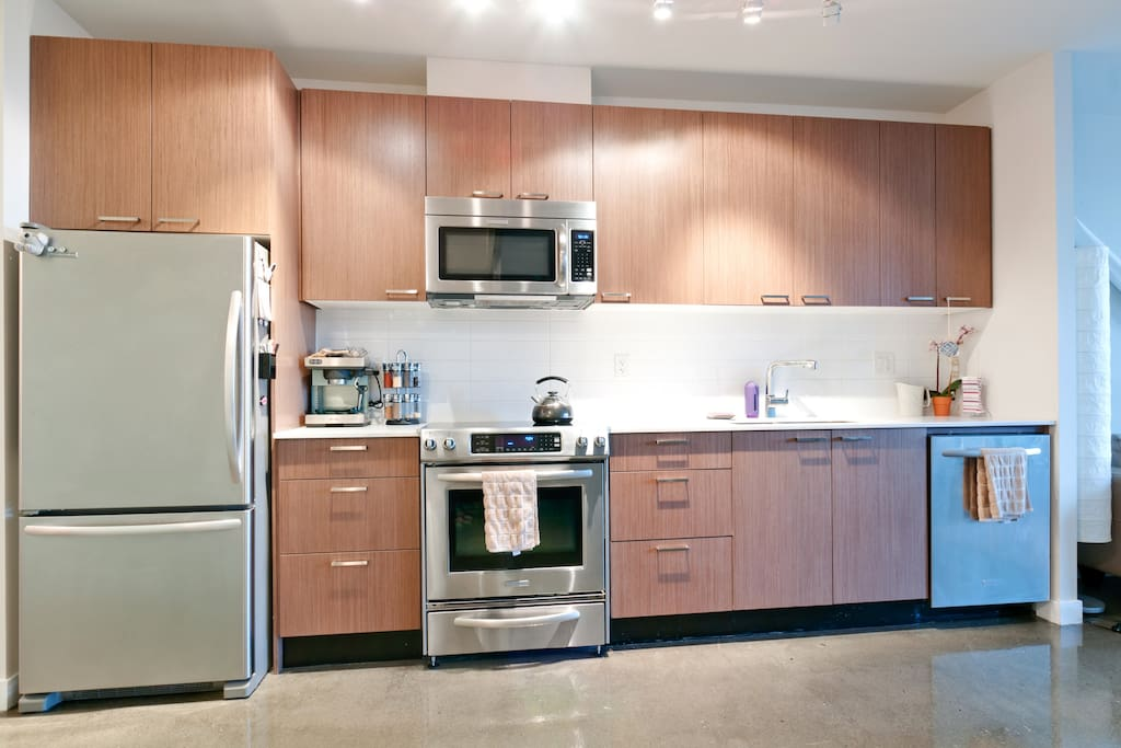Modern kitchen, stainless steel appliances including dishwasher and deep double sink.