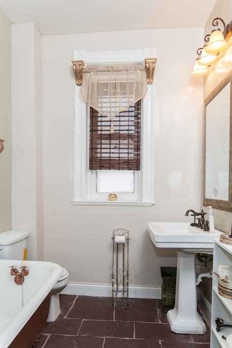 Private bathroom with an antique, clawfoot tub and shower