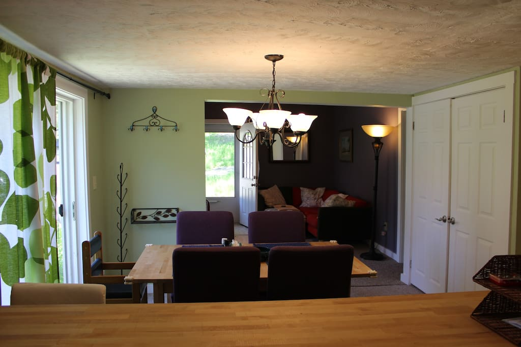 Looking at the dining room and onto the living room from the kitchen. Sliding glass doors to patio give lots of light in the daytime.