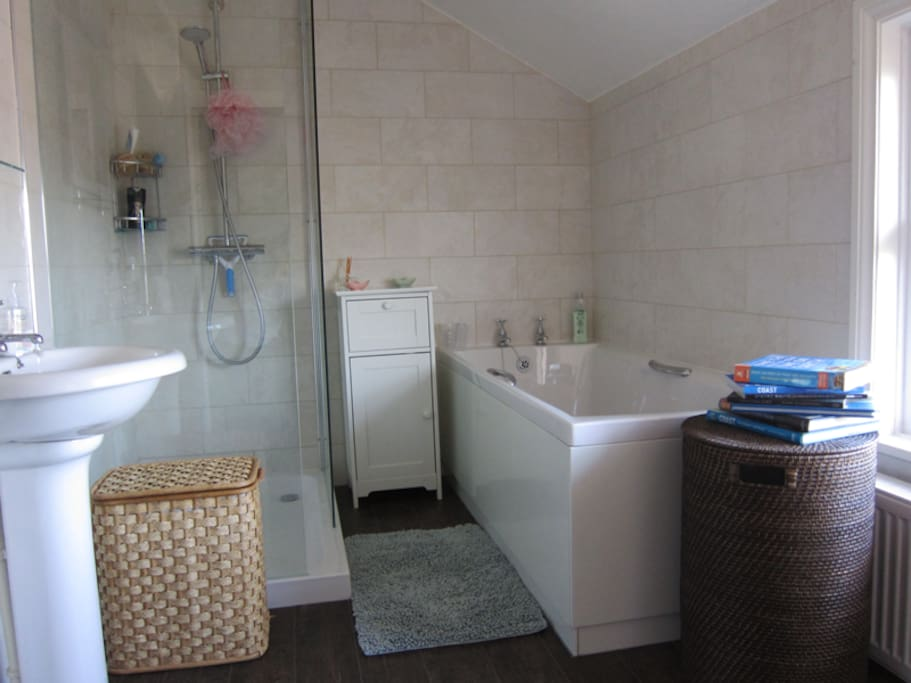 Fresh, spacious bathroom with bath and shower.