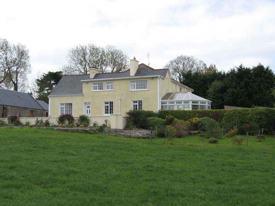 View of the House from the roadside field showing new conservatory, trees and old farm building