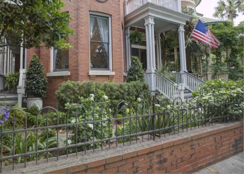 Garden and original wrought iron fence in front of house