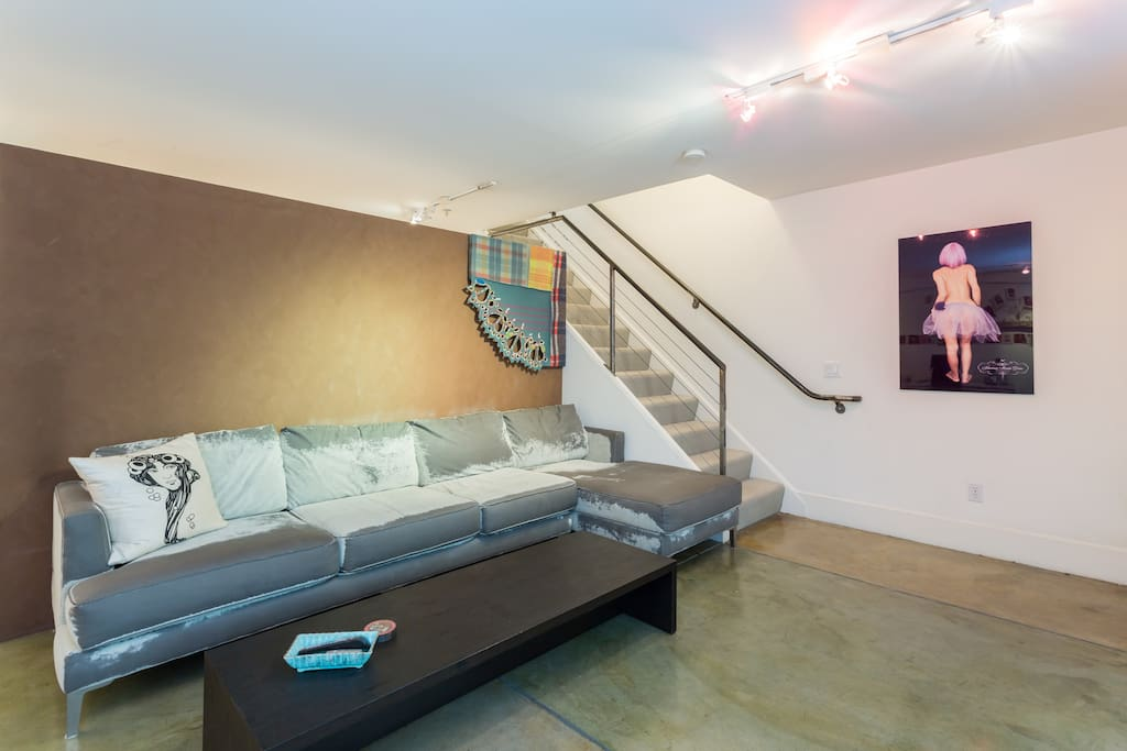 Living room area with 10 foot sectional couch that is also very deep and comfortable to sleep on. Couch faces the new flat screen TV with wall of windows. The stairs go to a locked door. The studio is on one floor.