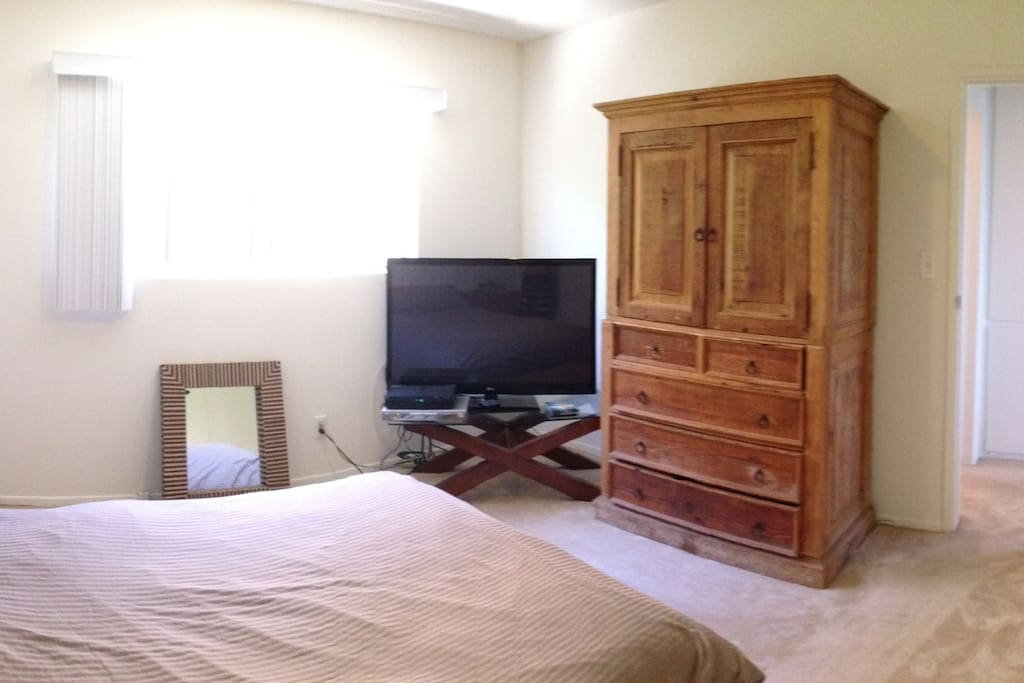 Bedroom with a queen size bed and 50 inch flat screen.
