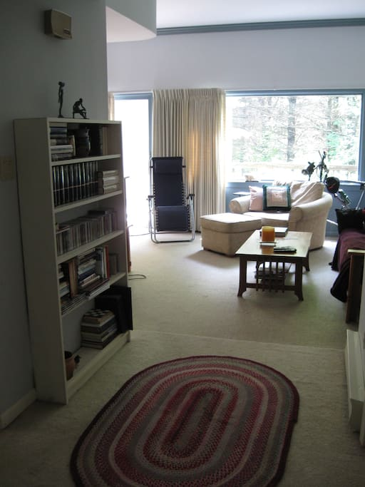 View of the living area from the front door. Windows look out toward the woods and private deck..
