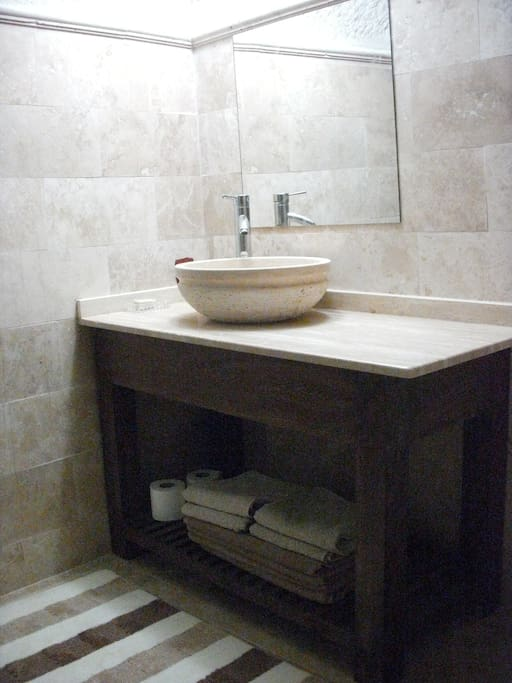 Sema cave travertine bathroom with shower.