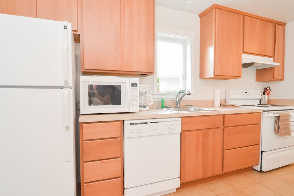 Kitchen with microwave dish washer and full size stove fully stocked for cooking meals.
