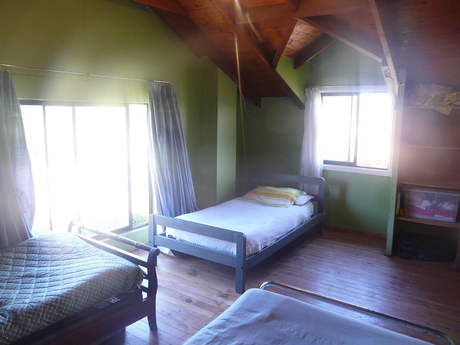 second floor bedroom with three beds and a big window