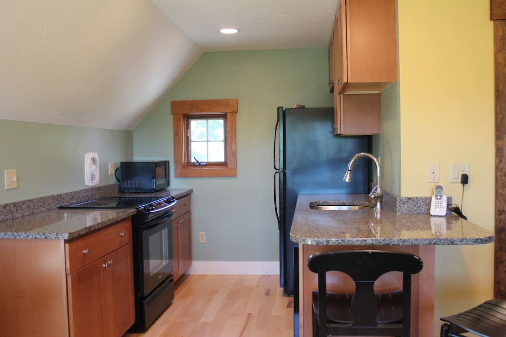 Kitchen has range, microwave, fridge with icemaker, dishwasher, and coffee maker.