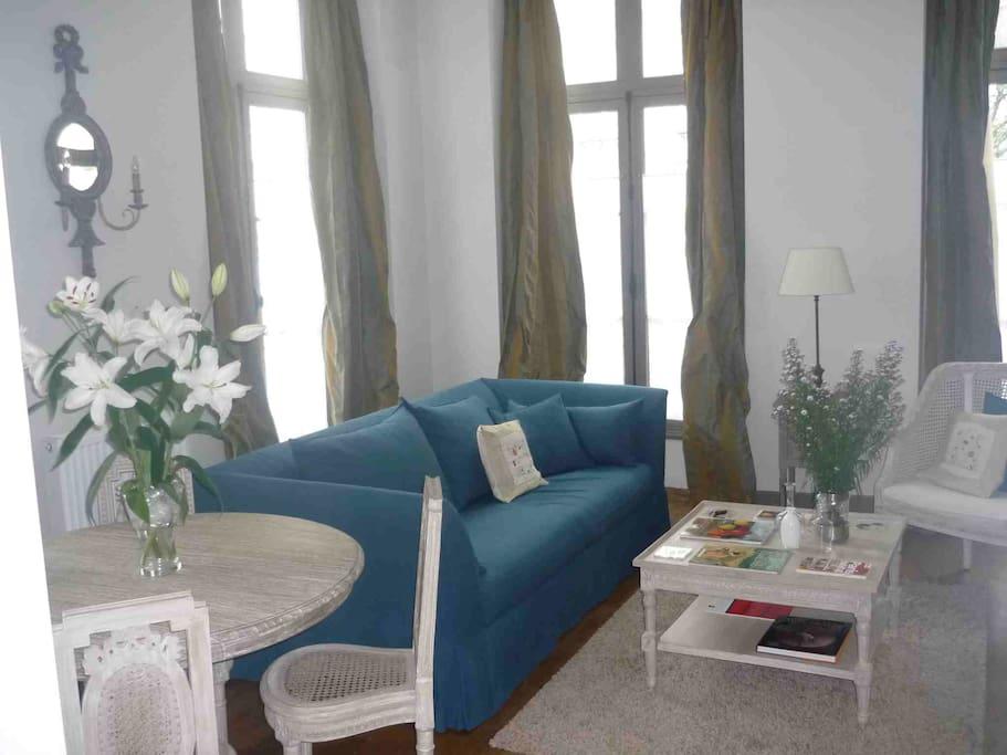 Corner living room, double exposure, high ceilings and windows, solid wood flooring.