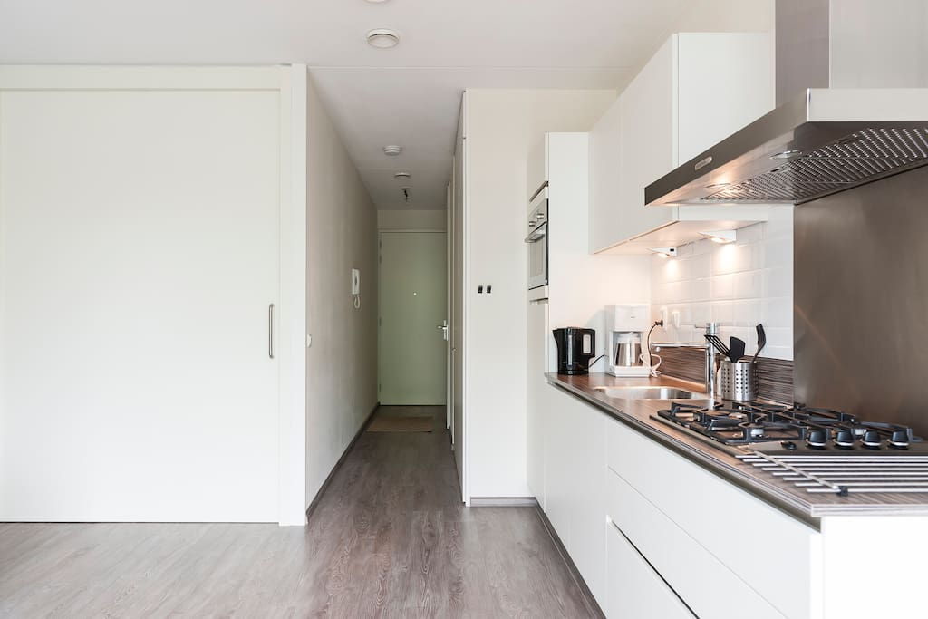The open plan kitchen comes with all the appliances you have at home.